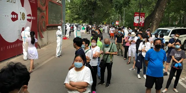 People wait in line at a COVID-19 testing site in Beijing on Wednesday after they were ordered by the government to be tested after potentially being exposed to the coronavirus at a wholesale food market. (AP)