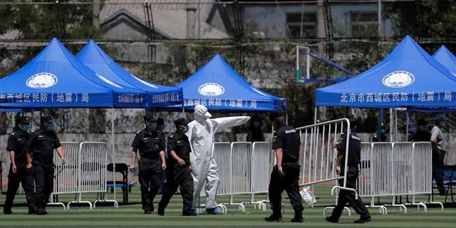 Работник направляет охранников, когда они устанавливают баррикады для людей, которые жили рядом с оптовым рынком Xinfadi, и тех, кто посещал рынок, чтобы провести тест на нуклеиновые кислоты на стадионе в Пекине, в воскресенье, 14 июня 2020 года.