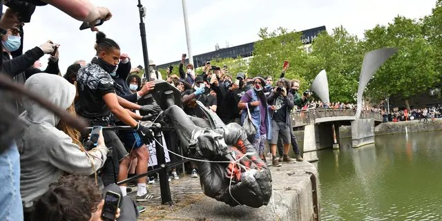 Protesters throw a statue of slave trader Edward Colston into Bristol harbor on Sunday. (AP)