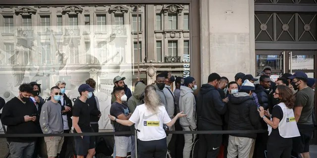 Nike employees speak to people lining up outside the Niketown shop in hopes of getting them to maintain social distancing in London on Monday. (AP)