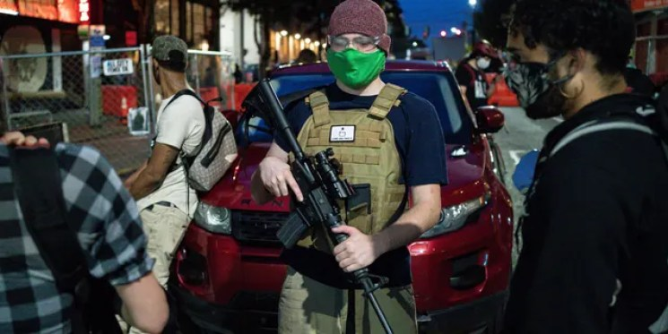 """A volunteer works security at an entrance to the so-called """"Capitol Hill Autonomous Zone"""" on June 10, 2020 in Seattle, Washington."""
