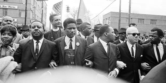 In this March 17, 1965, file photo, Dr. Martin Luther King Jr., fourth from left, foreground, locks arms with his aides as he leads a march of several thousand to the courthouse in Montgomery, Ala. From left are: an unidentified woman, Rev. Ralph Abernathy, James Foreman, King, Jesse Douglas Sr. and John Lewis. (AP Photo/File)