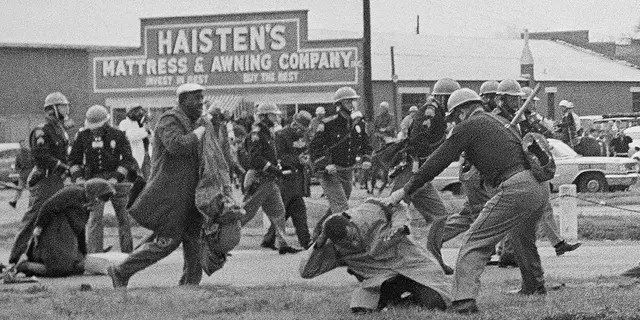 In this March 7, 1965, file photo, a state trooper swings a billy club at John Lewis, right foreground, chairman of the Student Nonviolent Coordinating Committee, to break up a civil rights voting march in Selma, Ala. Lewis sustained a fractured skull. (AP Photo/File)