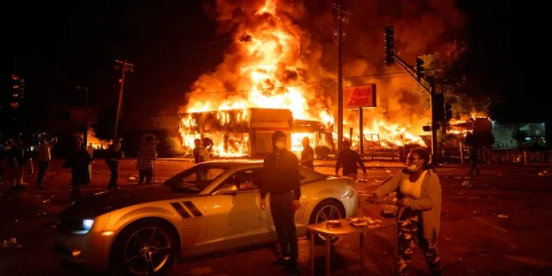 An AutoZone store burns as protesters gather outside of the Third Precinct in Minneapolis on Thursday, May 28, 2020. (Mark Vancleave/Star Tribune via AP)