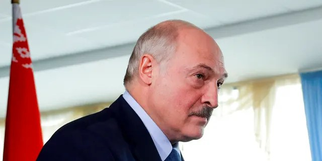 Belarusian President Alexander Lukashenko walks after voting at a polling station with a Belarusian national flag on the left, during the presidential election in Minsk, Belarus, Sunday, Aug. 9, 2020.