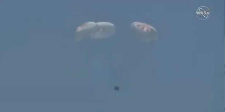 The capsule with its four main parachutes open.