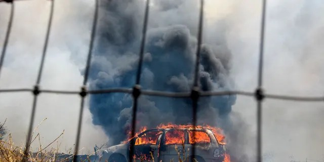 A brush fire burns a car at the Apple Fire in Cherry Valley, Calif., Saturday, Aug. 1, 2020.