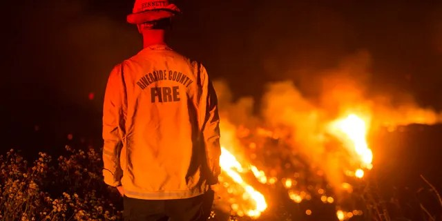A firefighter watches a brush fire at the Apple Fire in Banning, Calif., Saturday, Aug. 1, 2020.