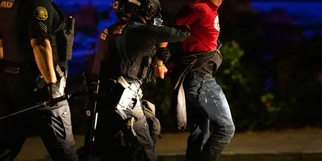 Portland police make arrests on the scene of the nightly protests at a Portland police precinct on Sunday, Aug. 30, 2020 in Portland, Ore.