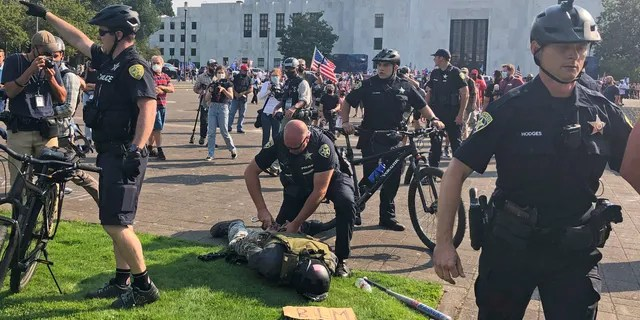 A protester is arrested during a protest at the Oregon State Capitol for a pro-Donald Trump rally at the Capitol in Salem, Ore. on Monday Sept. 7, 2020. (Associated Press)
