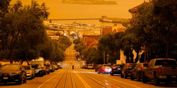 Under a sky deepened by the smoke of wildfires, a man crosses Hyde Street along the Alcatraz Island and Fisherman's Wharf in the background September 9 in San Francisco.  (AP Photo / Eric Risberg)