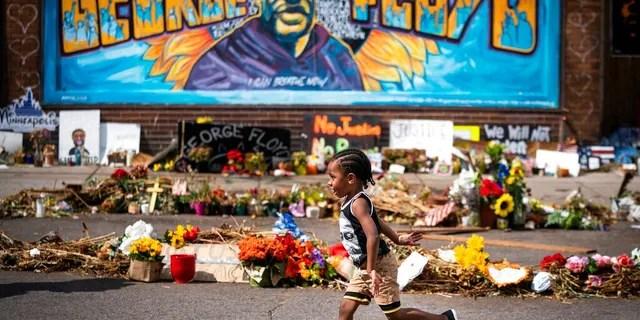 Carter Sims, 3, of Pine Island ran past a mural at the George Floyd memorial outside Cup Foods. LEILA NAVIDI • leila.navidi@startribune.com