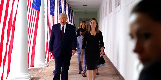 President Donald Trump walks along the Colonnadewith Judge Amy Coney Barrett after a news conference to announce Barrett as his nominee to the Supreme Court, in the Rose Garden at the White House, Sept. 26, in Washington.