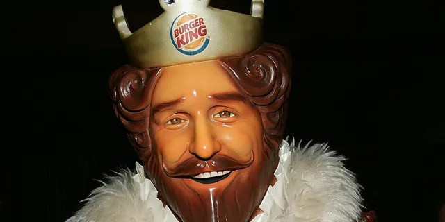 The advertisement has the mascot from Burger King appearing to make-out with the McDonald's mascot, Ronald McDonald.