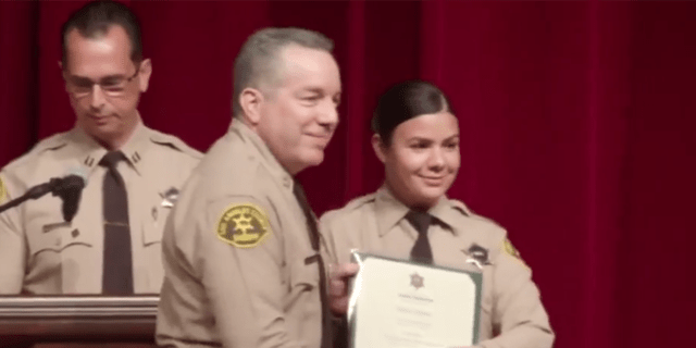 Claudia Apolinar smiling for a photo with LASD Sheriff Alex Villanueva at her July 2019 graduation (Los Angeles County Sheriff's Department Facebook)