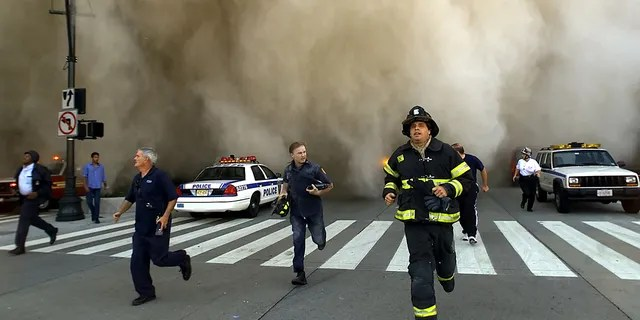 Policemen and firemen run away from the huge dust cloud caused as the World Trade Center's Tower One collapses after terrorists crashed two hijacked planes into the twin towers, September 11, 2001 in New York City. (Photo by Jose Jimenez/Primera Hora/Getty Images)