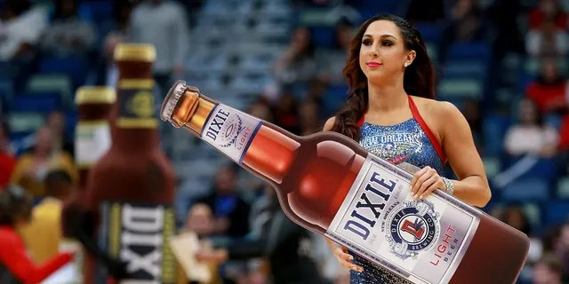 A New Orleans Pelicans cheerleader holds a Dixie beer during the first half of a NBA game between the Charlotte Hornets and the New Orleans Pelicans in March 2018.(Photo by Sean Gardner/Getty Images)