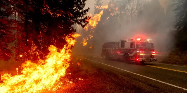 A firetruck drives along state Highway 168 while battling the Creek Fire in the Shaver Lake community of Fresno County, Calif., on Monday, Sept. 7, 2020.