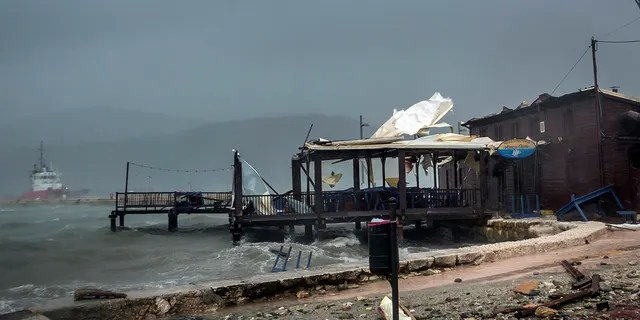 Waves crash into a seaside taverna during a storm at the port of Argostoli, on the Ionian island of Kefalonia, western Greece, Friday, September 18, 2020.