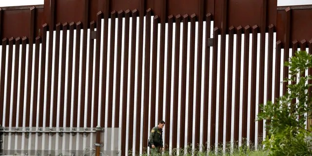 FILE - In this March 18, 2020, file photo, a Border Patrol agent walks along a border wall separating Tijuana, Mexico, from San Diego, in San Diego. Vice President Mike Pence in March directed the nation's top disease control agency to use its emergency powers to effectively seal the U.S. borders, overruling the agency's scientists who said there was no evidence the action would slow the coronavirus, according to two former health officials. (AP Photo/Gregory Bull, File)