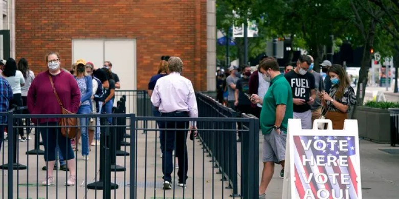 Voters line up and wait to cast a ballot at the American Airlines Center during early voting Thursday, Oct. 15, 2020, in Dallas. (AP Photo/LM Otero)