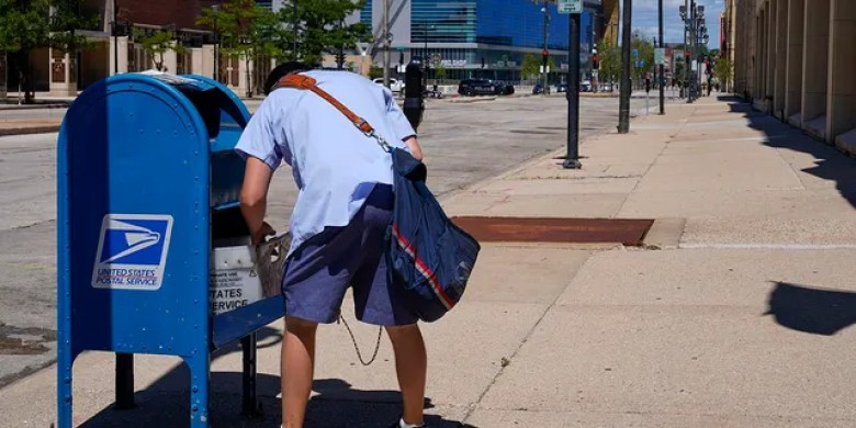 FILE - In this Aug. 18, 2020, file photo, a postal worker empties a box near the Fiserv Forum in Milwaukee. (AP Photo/Morry Gash, File)