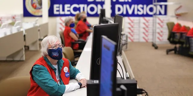 Election Judge, Mary Ann Thompson, is in front, checking the ballots in the auxiliary section at the Denver Election Division in Denver, Colorado on Thursday.  October 29, 2020. (Photo by Hyoung Chang / MediaNews Group (Denver Post via Getty Image)