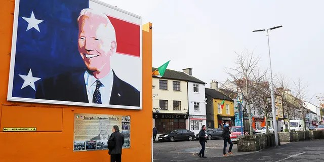 A man stops to read a plaque below a mural of US presidential candidate Joe Biden in his ancestral home of Ballina, Ireland, Thursday, Nov. 5, 2020. (Brian Lawless/PAvia AP)