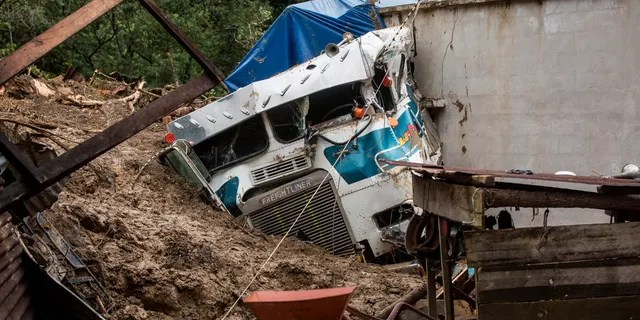 A semi-trailer is partially buried in a massive rain-fed landslide in the village of Queja, Guatemala, Saturday, November 7, 2020, in the wake of tropical storm Eta.