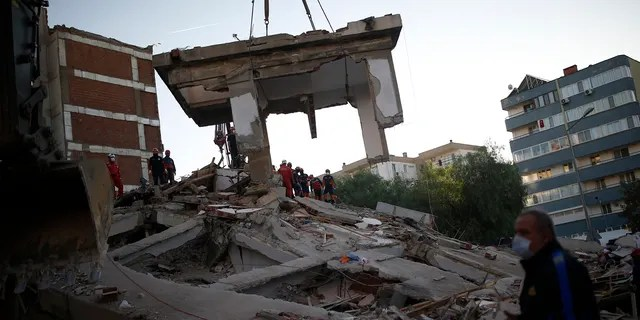 Members of rescue services search for survivors in the debris of a collapsed building in Izmir, Turkey, Saturday, Oct. 31, 2020.