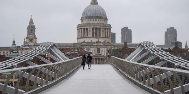 People walk across the Millennium Bridge in London until Monday, December 21, 2020.  Millions of people in England have learned that they must cancel their Christmas as well as holidays and shopping trips.  (Dominic Lipinski / PA via AP)