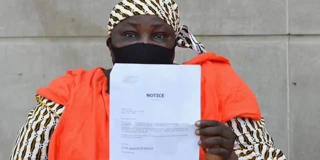 "Manty S. Kaba holds up a notice to pay an outstanding balance of her rent from her apartments' property management company, during a protest against evictions and in support of the movement to ""cancel rent"" outside the Bronx housing court on August 10, 2020 (Angela Weiss/AFP via Getty Images)"