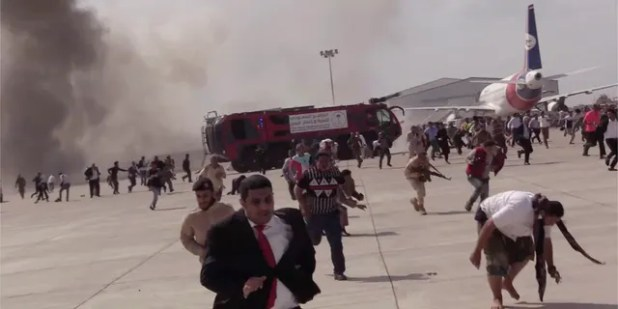 People flee after the explosion at Aden Airport.  At least 16 people have been reported killed.  (AP)