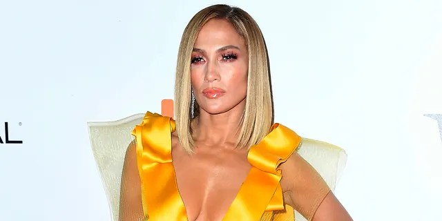 Jennifer Lopez showed off a hilarious photo showing her living her best life in the tropics versus returning home to the United States in a puffy jacket.