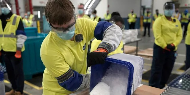 Dry ice is poured into a box containing the Pfizer-BioNTech COVID-19 vaccine as it is prepared to be shipped at the Pfizer Global Supply Kalamazoo manufacturing plant in Portage, Mich., Sunday, Dec. 13, 2020. (AP Photo/Morry Gash, Pool)