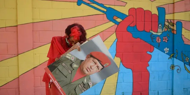 "A government supporter known as ""Caperucita,"" or Little Red Riding Hood, holds a photo of late Venezuelan President Hugo Chavez. (AP Photo/Matias Delacroix)"