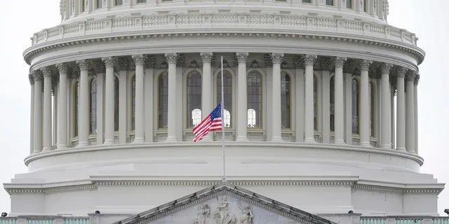 An American flag flies at half-staff in remembrance of U.S. Capitol Police Officer Brian Sicknick above the Capitol Building in Washington on Friday. A Pennsylvania teacher has been put on leave pending an investigation into his involvement in the protest before the riot in the Capitol. (AP Photo/Patrick Semansky)