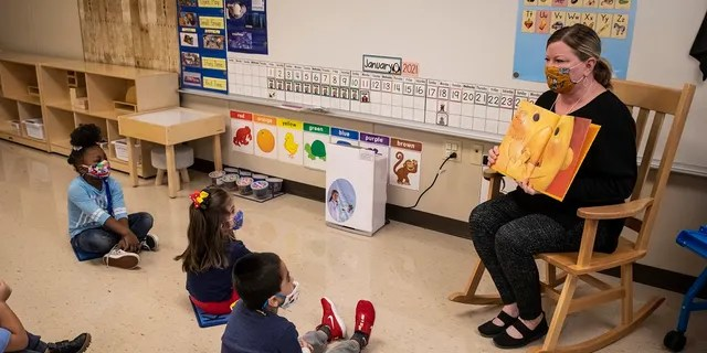 In this Jan. 11 file photo, pre-kindergarten teacher Angela Panush reads a story to her students at Dawes Elementary in Chicago. (Ashlee Rezin Garcia/Chicago Sun-Times via AP, Pool File)