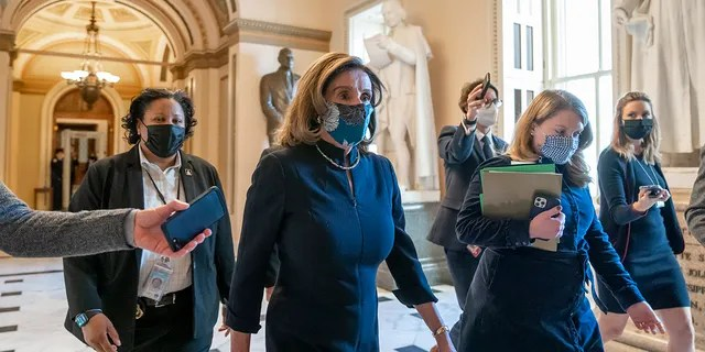 Speaker of the House Nancy Pelosi, D-Calif., returns to her leadership office after opening debate on the impeachment of President Donald Trump, at the Capitol in Washington, Wednesday, Jan. 13, 2021. (AP Photo/J. Scott Applewhite)