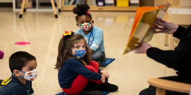 Pre-kindergarten students listen as their teacher reads a story at Dawes Elementary in Chicago, on Jan. 11. (AP/Chicago Sun-Times)
