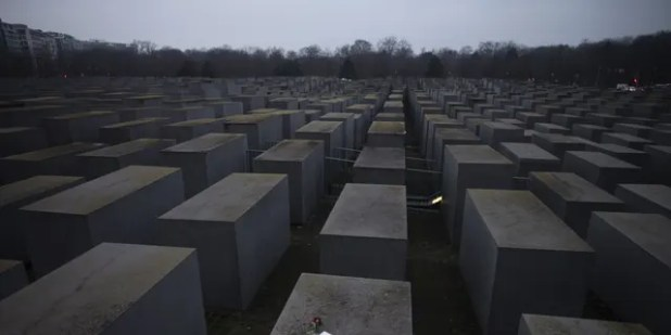 """Roses with a note """"#we remember"""", Berlin, Germany, is placed on the Holocaust Memorial on Wednesday, January 27, 2021 on International Holocaust Remembrance Day.  (AP Photo / Marcus Schreber)"""