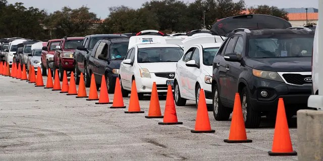 Hundreds of cars arrive through NRG Park to receive food supplies during the Neighborhood Super Site food delivery event held at Houston Food Bank and HISD, Sunday, February 21, 2021, Houston.  (Via Mary D. D. Jesús / Houston Chronicle AP)