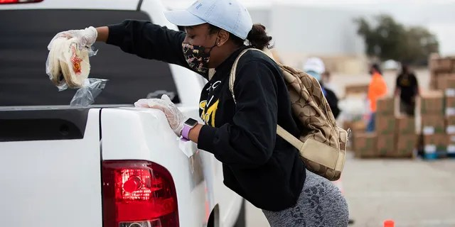 The Houston Food Bank and HISD place a packet of tortillas on a Volunteer Taiya Edwards vehicle at the age of 18 during a Neighborhood Super Sight food distribution event held in Houston, Sunday, February 21, 2021.  (Via Mary D. D. Jesús / Houston Chronicle AP)