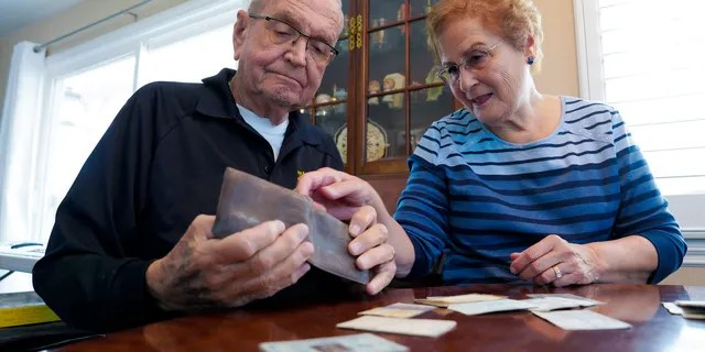 Paul Grisham and his wife Carole Salazar look over his wallet and the items that were inside when he lost the wallet back in 1968. (Nelvin C. Cepeda/The San Diego Union-Tribune via AP)