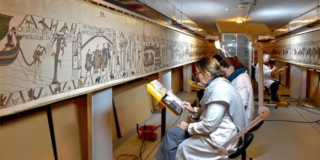 This photo, provided by Bycom Townhall, shows technicians working at the tapestry on 8 November 2020 in Beaumake, Normandy.  (Ville de Beaux via AP)