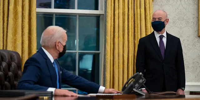 Secretary of Homeland Security Alejandro Mayorkas listens as President Joe Biden speaks before signing an executive order on immigration, in the Oval Office of the White House, Tuesday, Feb. 2, 2021, in Washington. (AP Photo/Evan Vucci)