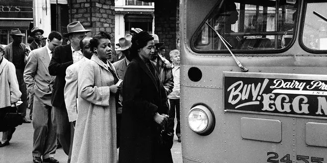 American civil rights activist Rosa Parks (center in dark coat and hat) waits to board a bus at the end of the Montgomery bus boycott, Montgomery, Alabama, December 26, 1956.
