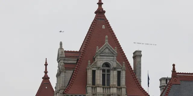 """A plane towing a banner that reads """"New Yorkers Say: Cuomo's Got to Go!"""" flies above the New York State Capitol in Albany, New York, U.S., March 17, 2021. REUTERS/Angus Mordant"""