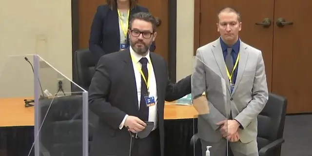 In this screen grab from video, defense attorney Eric Nelson, left, defendant and former Minneapolis police officer Derek Chauvin, right, introduce themselves to jurors as Hennepin County Judge Peter Cahill presides over jury selection in the trial of Chauvin Wednesday, March 17, 2021. (Court TV, via AP, Pool)