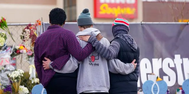 Mourners console each other along the temporary fence line outside the parking lot of a King Soopers grocery store, the site of a mass shooting in which 10 people died, Friday, March 26, 2021, in Boulder, Colo.